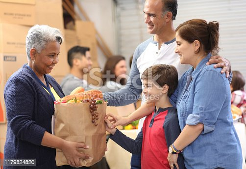 Multi-ethnic, mixed age group of volunteers work together at food bank.  They pack sacks and boxes of food for needy people in their community.  Senior woman gives sack full of groceries to needy family.
