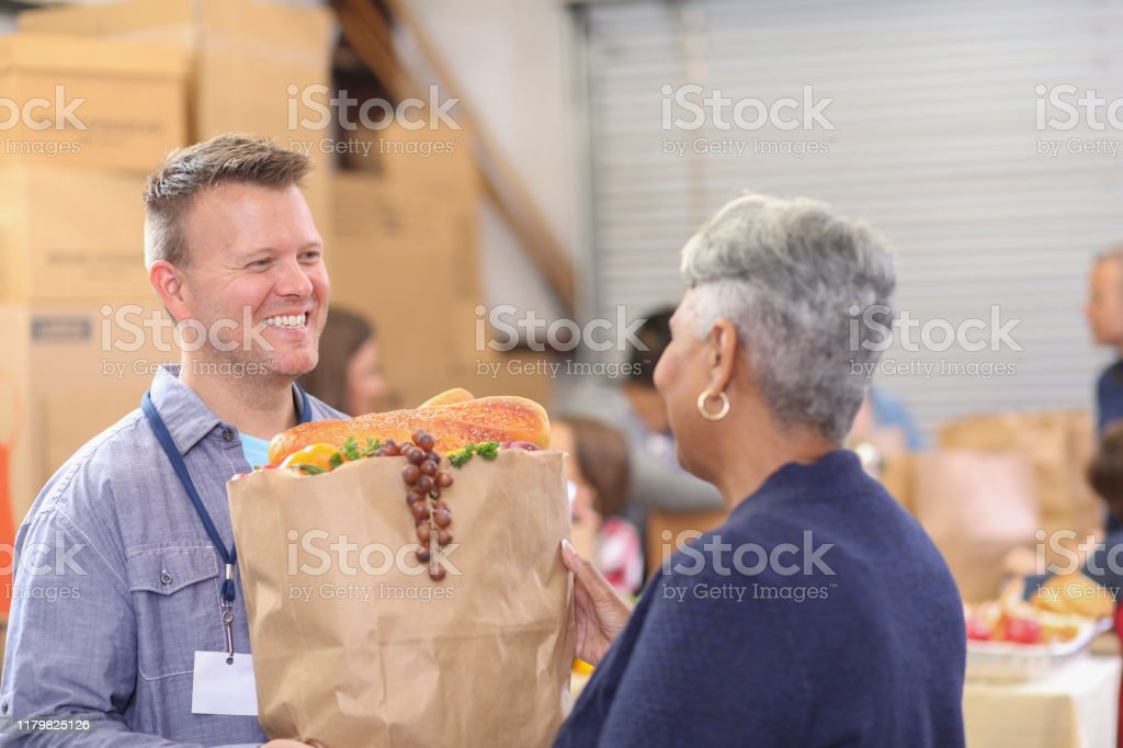 Multi-ethnic group of volunteers work at food bank. Multi-ethnic, mixed age group of volunteers work together at food bank.  They pack sacks and boxes of food for needy people in their community.  Man gives sack full of groceries to senior woman. A Helping Hand Stock Photo
