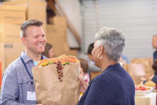Multiethnic Group Of Volunteers Work At Food Bank Stock Photo - Download Image Now