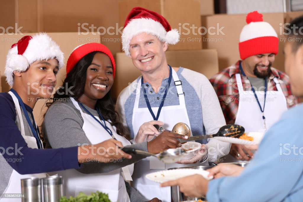 Multi-ethnic group of volunteers work at soup kitchen at Christmas. Multi-ethnic, mixed age group of volunteers work together at food bank, soup kitchen during Christmas season.  They serve food to needy people in their community at holiday times. A Helping Hand Stock Photo