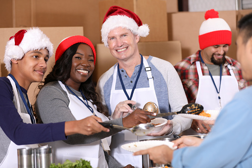 Multiethnic Group Of Volunteers Work At Soup Kitchen At Christmas Stock Photo - Download Image Now