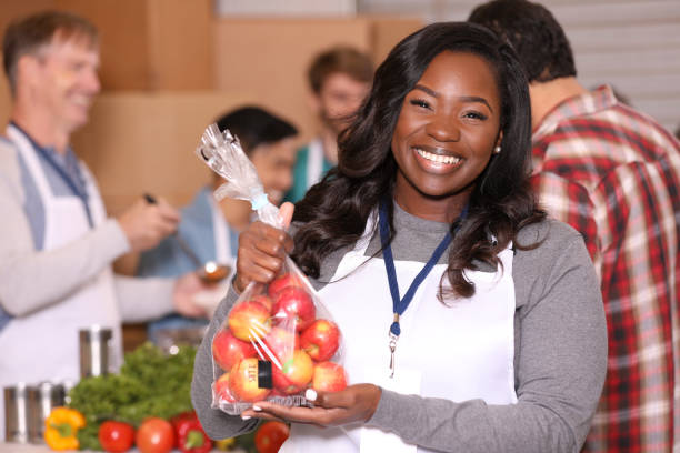 Multi-ethnic group of volunteers work at soup kitchen, food bank. stock photo
