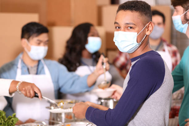 Multi-ethnic group of volunteers work at soup kitchen. stock photo