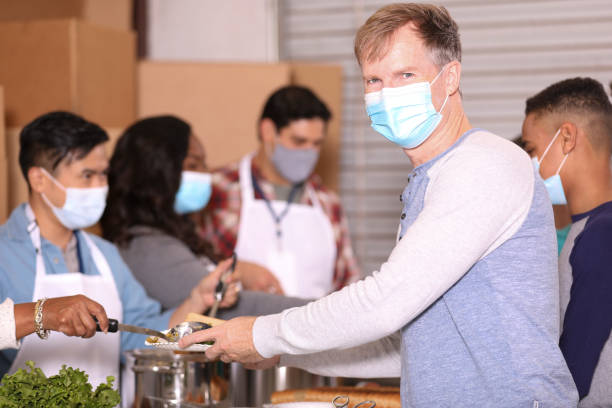 Multi-ethnic group of volunteers work at soup kitchen. Multi-ethnic, mixed age group of volunteers work together at food bank, soup kitchen.  They serve food to needy people in their community. Hungry mature man receives plate of food foreground. Face masks. covid-19 stock pictures, royalty-free photos & images