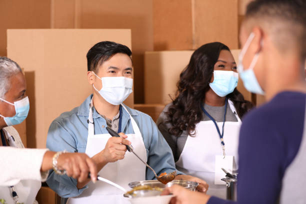 Multi-ethnic group of volunteers work at soup kitchen. Multi-ethnic, mixed age group of volunteers work together at food bank, soup kitchen.  They serve food to needy people in their community. Face masks. covid-19 stock pictures, royalty-free photos & images