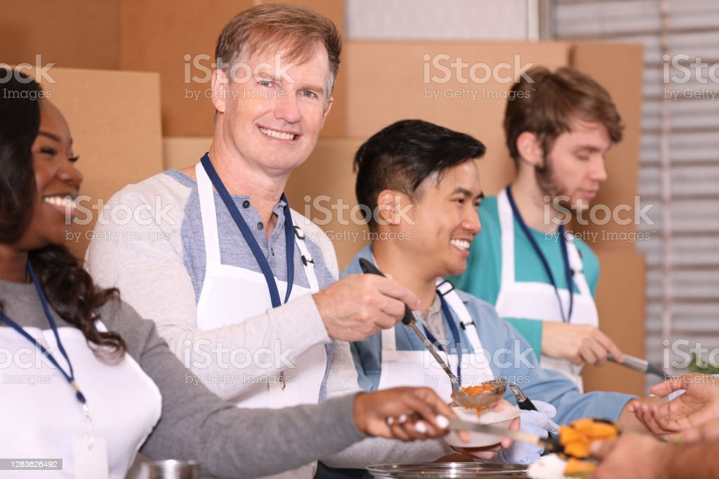 Multi-ethnic group of volunteers work at soup kitchen. Multi-ethnic, mixed age group of volunteers work together at food bank, soup kitchen.  They serve food to needy people in their community. A Helping Hand Stock Photo