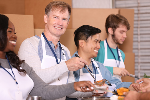 Multiethnic Group Of Volunteers Work At Soup Kitchen Stock Photo - Download Image Now