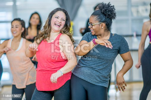 A group of young multi-ethnic women are participating in a Zumba class.  They are all wearing their active wear, smiling and having fun.  The two women in front are bumping hips and sharing a laugh.