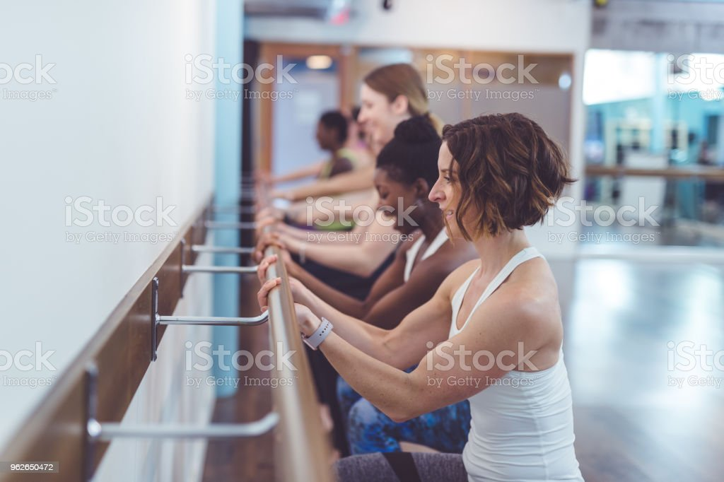 Multiethnic group of women do a barre workout together in a modern health club stock photo