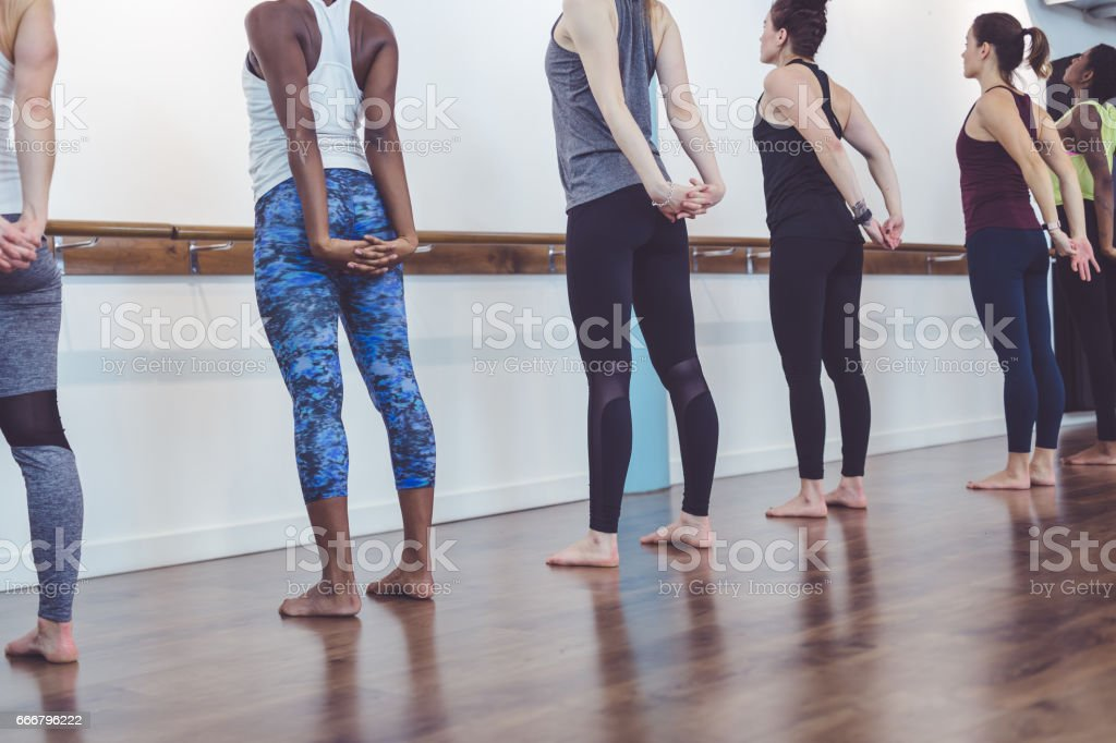 Multi-ethnic group of women doing barre workout stock photo