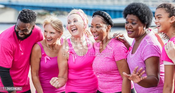A multi-ethnic group of five women and a man wearing pink shirts, participating in a charity event to raise money for breast cancer research. They are standing side by side on a city waterfront, smiling.