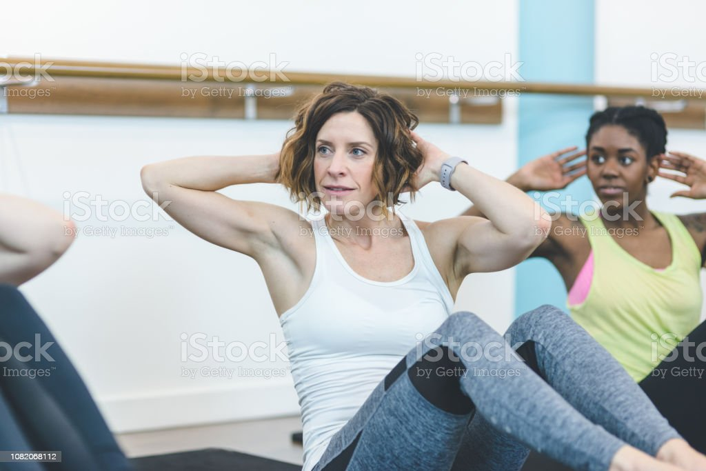 A multiethnic group of young women do a workout together at a modern...