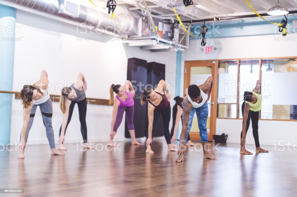 A multiethnic group of women in their 30s work out together in a...