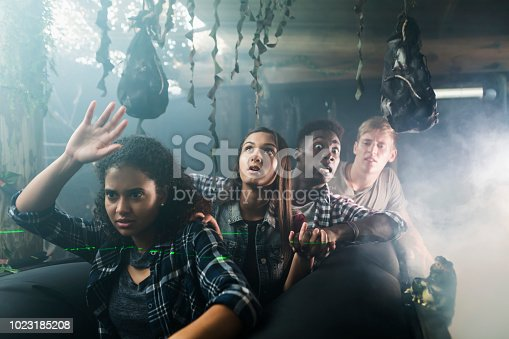 A group of four multi-ethnic teenagers and young adults in a halloween haunted house, on a ride through a dark, creepy tunnel.