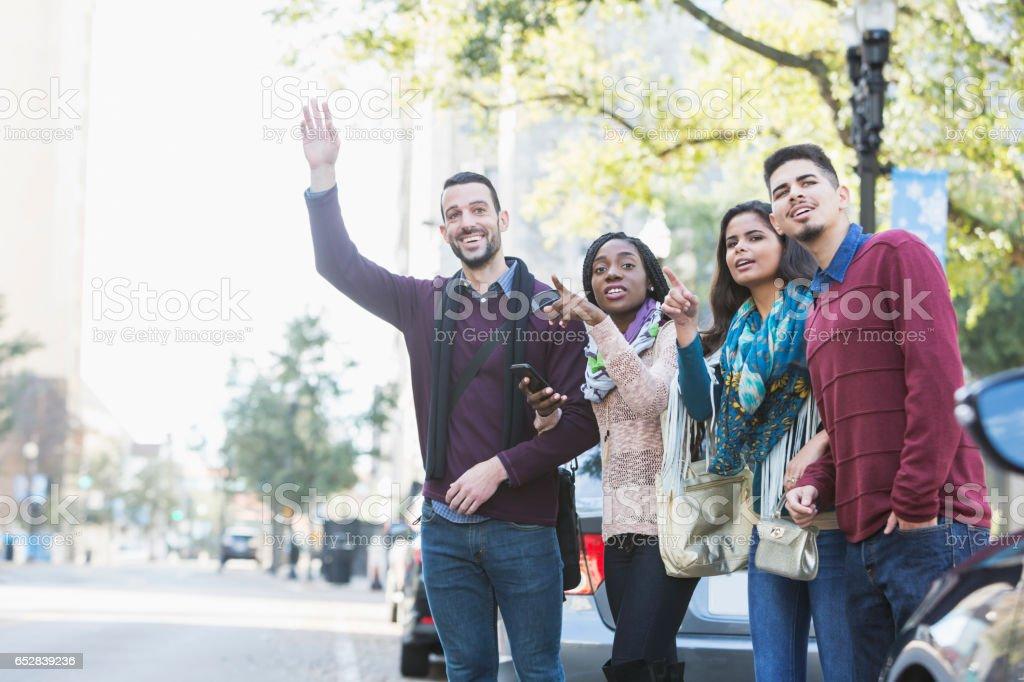 Grupo multiétnico de jovens adultos esperando carona - foto de acervo