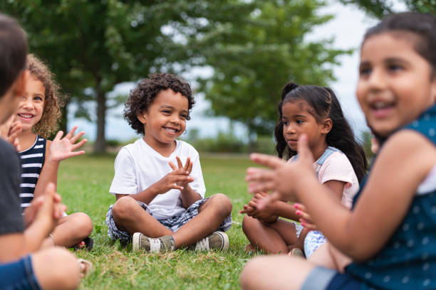A Multi-Ethnic Group of Young Children are Clapping Outside An adorable group of multi-ethnic children are outside sitting in the grass one sunny afternoon. They are clapping and smiling while sitting cross-legged and singing a song. recess stock pictures, royalty-free photos & images