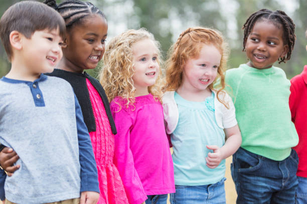 Multi-ethnic group of young children standing in the park stock photo