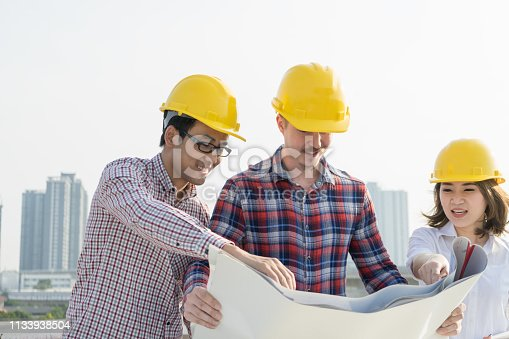 1047558948istockphoto Multiethnic group of young civil engineers , worker and architects discussing on drawing/blueprint construction with highrise building background, wearing safety yellow helmet. Inspection concept. 1133938504