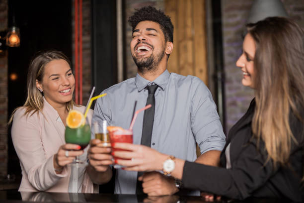 multi-ethnic group of young people having fun in the bar - after work stock photos and pictures