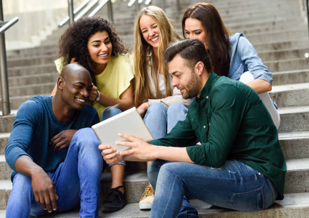 Multi-ethnic group of young people looking at a tablet computer stock photo