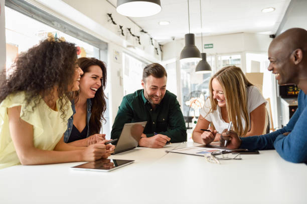 Multi-ethnic group of young people studying together on white desk stock photo