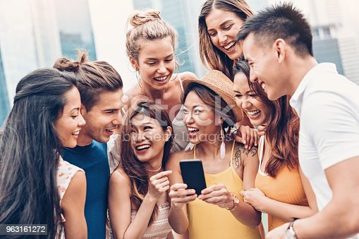 istock Multi-ethnic group of young people with smart phone 963161272