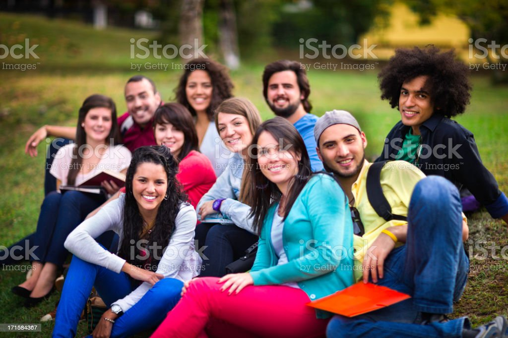 Multi-ethnic group of young students sharing at university campus stock photo