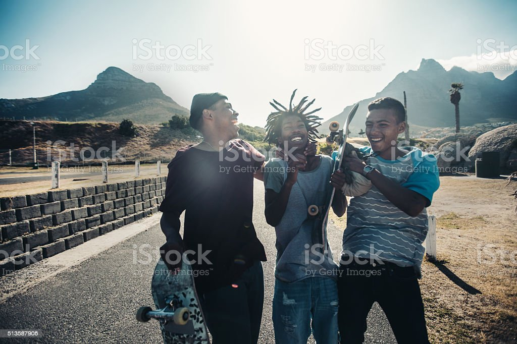 Multi-Ethnic Group Skaters Laughing Together at Seaside stock photo
