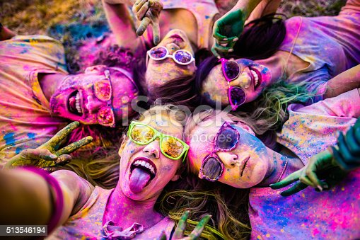 Multi-Ethnic group covered in colorful powder lay in grass taking a selfie in a park at a Holi festival in the summer