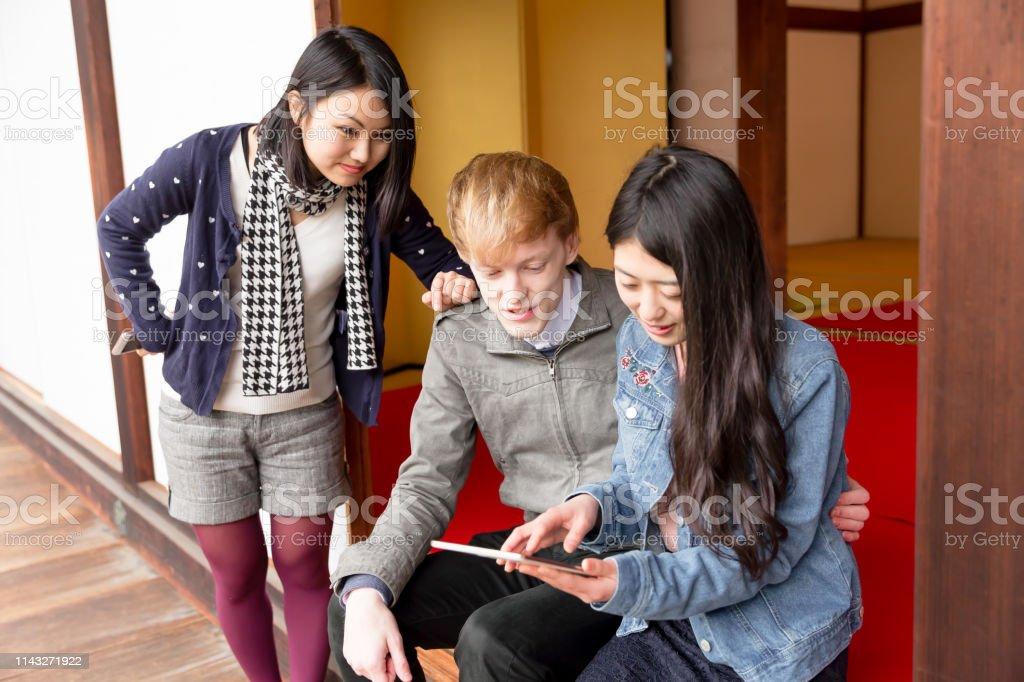 テンプルでデジタルテーブルを使用した多民族グループ ストックフォト