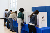 An unrecognizable mutli-ethnic group of voters stands to vote at the voting booths lined up against the wall of the gym.