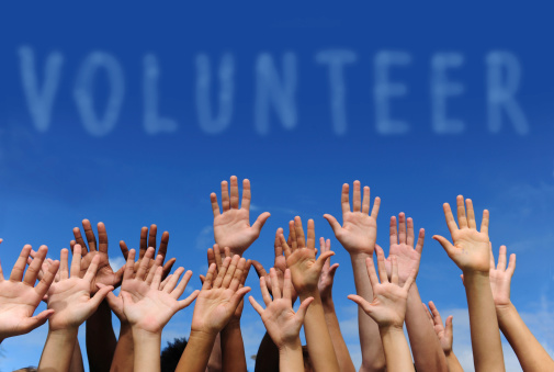 multi-ethnic volunteer group raising hands against blue sky