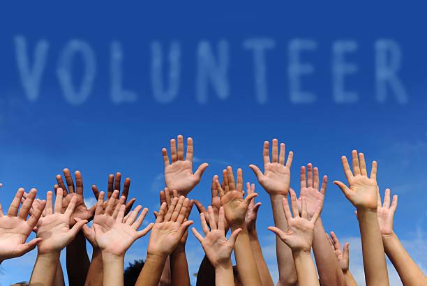 "Multiethnic hands raised under word ""volunteer"" multi-ethnic volunteer group raising hands against blue sky volunteer stock pictures, royalty-free photos & images"