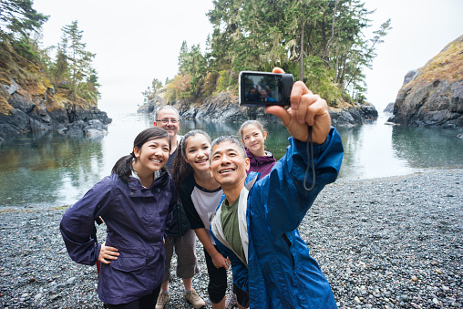 A real extended family of multi-ethnic and multi-generational backpackers in the wilderness pose of a selfie on a deserted beach surrounded by islands and forest with the ocean in the background.  Rainy day in a wilderness park.  Whiffen Spit, Sooke, British Columbia, Canada.
