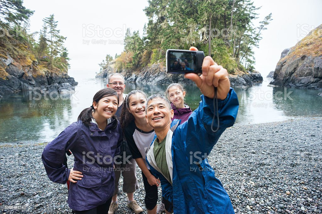 Multi-Ethnic Hiking Family Posing for Selfie on Remote Wilderness Beach stock photo