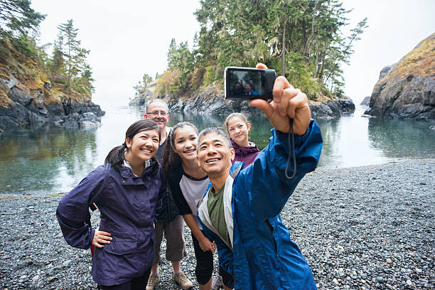 multi-ethnic hiking family posing for selfie on remote wilderness beach - canada travel stock photos and pictures