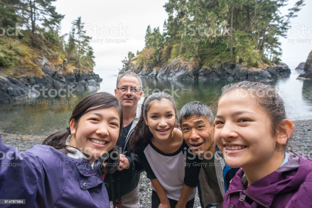 Multi-Ethnic Hiking Family Posing for Selfie on Rugged Wilderness Beach stock photo