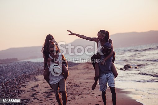 istock Multi-ethnic hipster couples giving piggy-back rides on beach at sunset 894383596