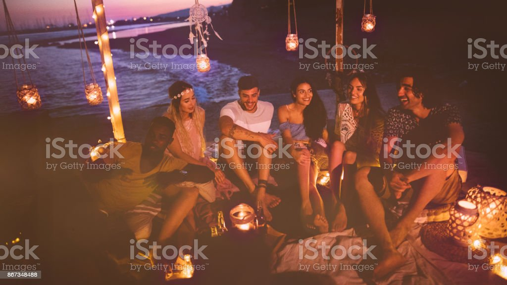 Multi-ethnic hipster couples having fun at summer night beach party stock photo