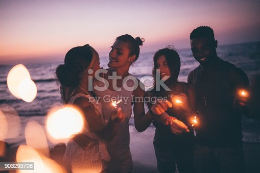 istock Multi-ethnic hipster friends and couples partying with sparklers at beach 903293708