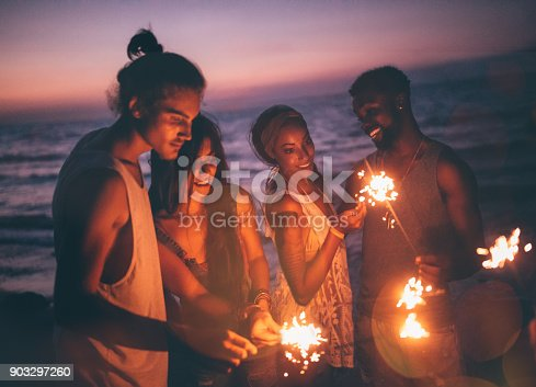 istock Multi-ethnic hipster friends celebrating with sparklers at beach party 903297260