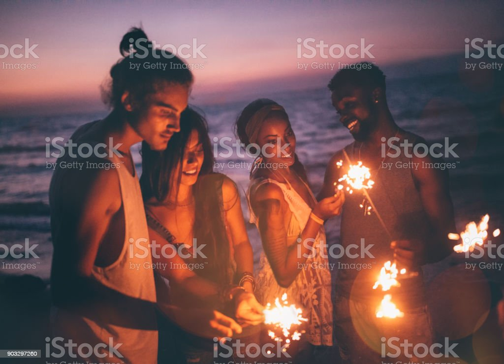 Multi-ethnic hipster friends celebrating with sparklers at beach party stock photo