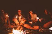 ビーチのキャンプファイヤーの周りに座って花火を祝う多民族流行に敏感な友人