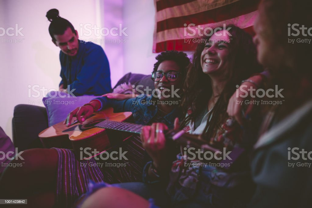 Multi-ethnic hipster friends playing the guitar and singing at home stock photo