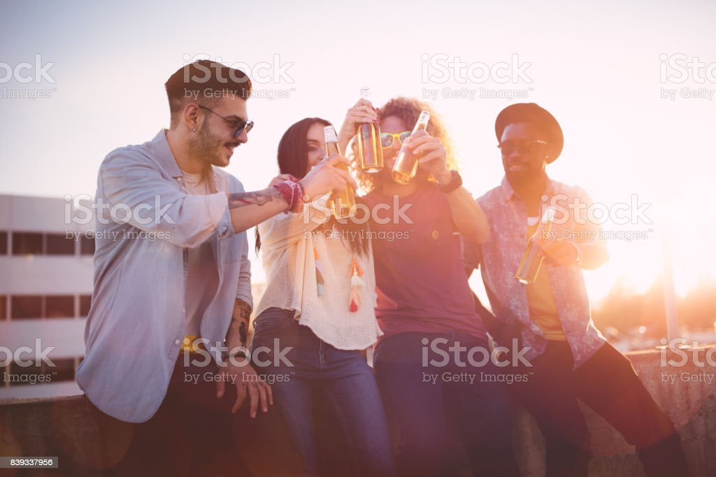 Multi-ethnic hipster friends toasting with beer at rooftop party stock photo