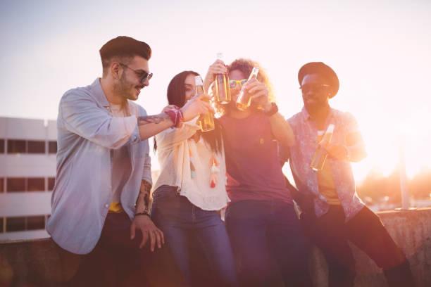 Amis de hipster multiethnique grillage avec de la bière à la fête sur le toit - Photo