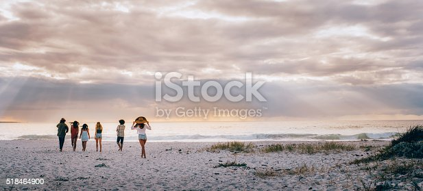 A Hipster multi-ethnic group of friends walking barefoot and happy on sandy beach towards sun beam lit ocean