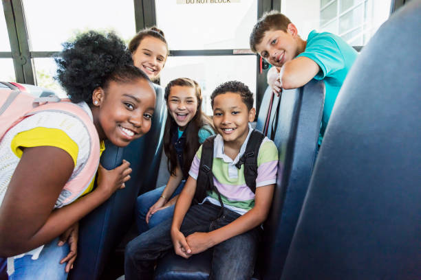 Multi-ethnic junior high students riding school bus stock photo