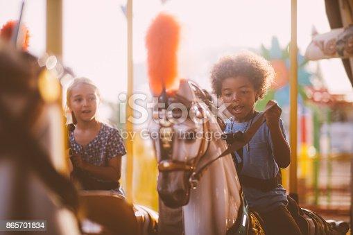 Multi-ethnic mixed family siblings having fun riding horses on funfair carousel ride in summer