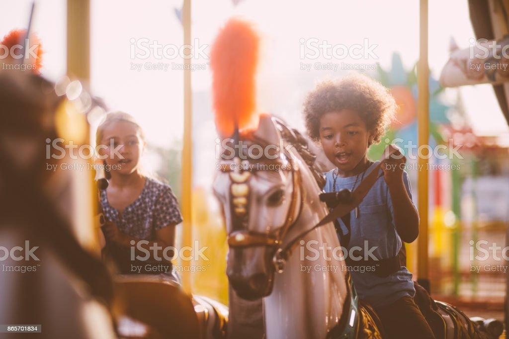 Multi-ethnic kids having fun on amusement park merry-go-round ride stock photo
